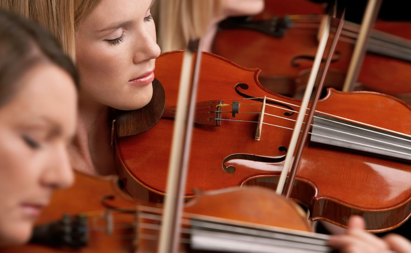 This is an image of a few girls playing the violin and relieving stress